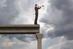 L'homme d'affaires regarde par un télescope Photographie stock