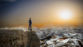 L'homme d'affaires regarde sur des piles des déchets, vue arrière photographie stock