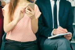 L'homme d'affaires remet l'écriture dans des mains de cahier de croquis et de fille faisant des notes dans le téléphone au plan r photos stock