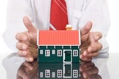 l'homme d'affaires remet la protection de maison images stock