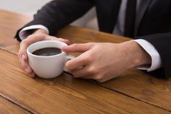 L'homme d'affaires remet le plan rapproché de pause-café Image stock