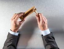 L'homme d'affaires remet tenir le hochet en bois pour le réveil téléphonique de bureau image libre de droits