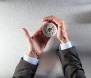 L'homme d'affaires remet tenir une boussole, contrôlant son orientation de carrière Photo stock