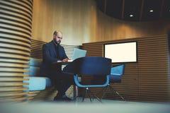 L'homme d'affaires sérieux dans le costume de luxe travaille sur l'ordinateur portable Photos libres de droits