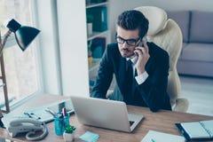L'homme d'affaires sérieux a une conversation téléphonique au travail Il I photo libre de droits