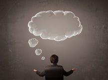 L'homme d'affaires s'asseyant avec le nuage a pensé au-dessus de sa tête Photo libre de droits