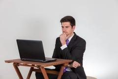 L'homme d'affaires s'assied pensivement sur un ordinateur portable Image libre de droits
