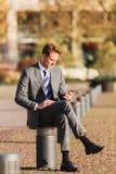 L'homme d'affaires s'assied sur un courrier avec un téléphone portable Photos stock