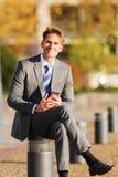 L'homme d'affaires s'assied sur un courrier avec un téléphone portable Photos libres de droits