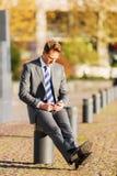 L'homme d'affaires s'assied sur un courrier avec un téléphone portable Photo libre de droits
