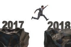 L'homme d'affaires sautant à partir de 2017 à 2018 Photographie stock libre de droits