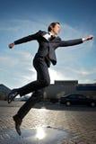 L'homme d'affaires sautant par-dessus le magma de l'eau sur la rue Photos libres de droits