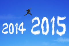 L'homme d'affaires sautant par-dessus le nuage de 2015 formes sur le ciel bleu Images stock