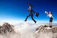 L'homme d'affaires sautant par-dessus une falaise et un coll?gue encourage avec le corne de brume image stock