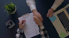L'homme d'affaires se réjouit à signer un contrat et serre la main à un associé s'asseyant à la table Projectile supplémentaire l banque de vidéos