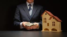 L'homme d'affaires se tient aux mains et compte une pile d'argent près d'un modèle de maison sur une table Photos stock