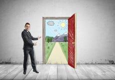 L'homme d'affaires se tient montrant la scène ensoleillée avec la route et les montagnes derrière une porte ouverte par les deux  photos stock
