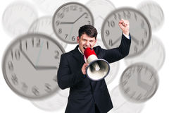 L'homme d'affaires se tient parmi des horloges Photos libres de droits