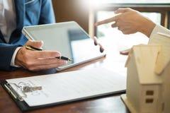 L'homme d'affaires signe le contrat derrière le modèle architectural à la maison Discussion avec un staffde location de société image stock