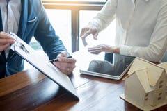 L'homme d'affaires signe le contrat derrière le modelDiscu architectural à la maison photo libre de droits