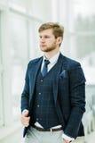 L'homme d'affaires songeur de nouveau venu dans un costume tient près de l'des WI Image stock