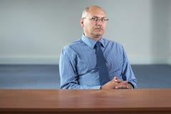 L'homme d'affaires aîné sérieux s'assied derrière le bureau vide Photos stock