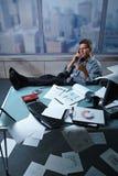 L'homme d'affaires sur des pieds d'appel lèvent des papiers tout autour Images stock