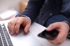 L'homme d'affaires sur son lieu de travail utilise un smartphone et Photos libres de droits