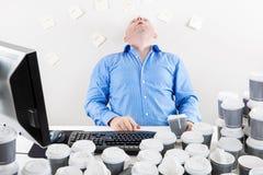 L'homme d'affaires surchargé boit de trop de café Photo stock