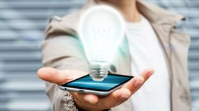 L'homme d'affaires tenant l'ampoule brillante au téléphone portable '3D rendent Photo libre de droits