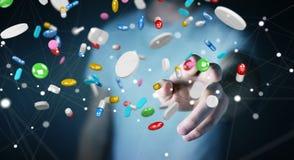 L'homme d'affaires tenant et touchant les pilules de flottement 3D de médecine les déchirent Photographie stock libre de droits