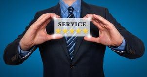 L'homme d'affaires tenant la carte blanche avec des étoiles du service cinq signent, bleu images stock