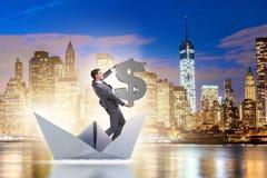 L'homme d'affaires tenant le bateau de bateau de papier d'équitation du dollar Images stock