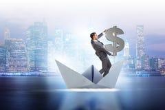 L'homme d'affaires tenant le bateau de bateau de papier d'équitation du dollar Image libre de droits