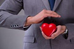L'homme d'affaires tenant le coeur rouge dans le concept d'amour Images stock