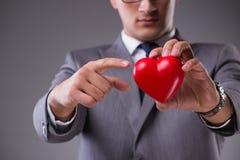 L'homme d'affaires tenant le coeur rouge dans le concept d'amour Images libres de droits