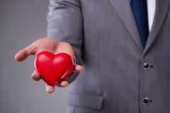 L'homme d'affaires tenant le coeur rouge dans le concept d'amour Photo libre de droits
