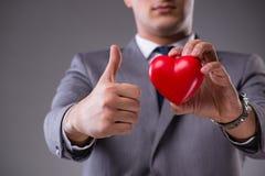 L'homme d'affaires tenant le coeur rouge dans le concept d'amour Photos stock