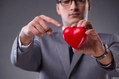 L'homme d'affaires tenant le coeur rouge dans le concept d'amour Image stock