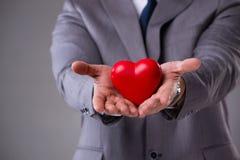 L'homme d'affaires tenant le coeur rouge dans le concept d'amour Photographie stock libre de droits