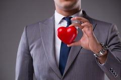 L'homme d'affaires tenant le coeur rouge dans le concept d'amour Photographie stock