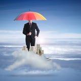 L'homme d'affaires tenant le parapluie d'arc-en-ciel pour protègent ses finances images libres de droits