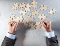 L'homme d'affaires tendu remet impatient pour relier des morceaux de puzzle pour des problèmes Photos stock