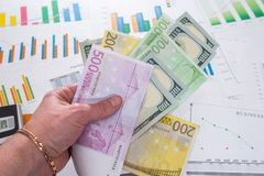 l'homme d'affaires tient l'argent sur le fond des graphiques de gestion Photographie stock libre de droits