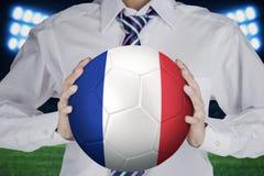L'homme d'affaires tient la boule avec un drapeau de Frances Photos libres de droits