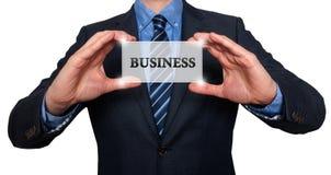 L'homme d'affaires tient la carte blanche avec le signe d'affaires, blanc - les actions P Photo libre de droits