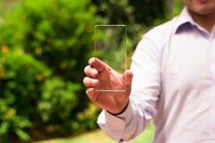 L'homme d'affaires tient le téléphone intelligent transparent futuriste dans sa main Images libres de droits