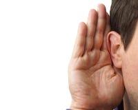 L'homme d'affaires tient sa main près de son oreille et écoute Photos stock