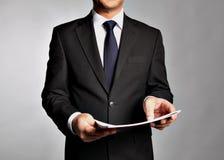 L'homme d'affaires tient un livret Image stock