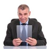 L'homme d'affaires tient un panneau transparent à son bureau Photographie stock libre de droits